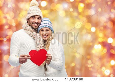 love, valentines day, couple, christmas and people concept - smiling man and woman in winter hats and scarf holding red paper heart shape over lights background