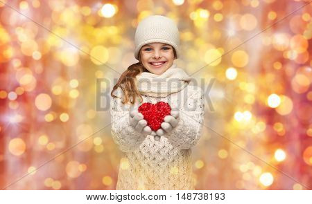 people, charity, holidays, children and love concept - smiling teenage girl in winter clothes with small red heart over lights background