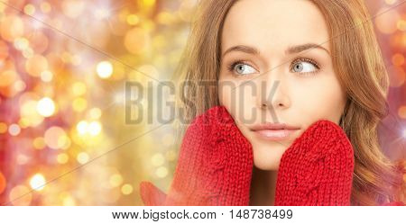 winter, holidays, christmas and people concept - close up of happy young woman in red mittens touching her face over lights background