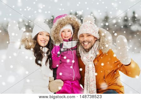 parenthood, fashion, gesture, season and people concept - happy family with child in winter clothes waving hands outdoors