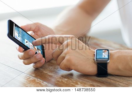 business, technology, internet, mass media and people concept - close up of male hands on wooden table holding smartphone and wearing smart watch with news web page on screen