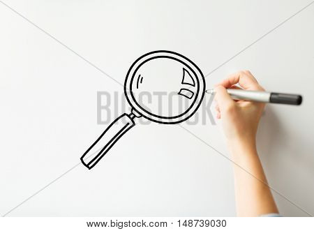 research, business, people and education concept - close up of hand with marker drawing magnifier on white board or wall