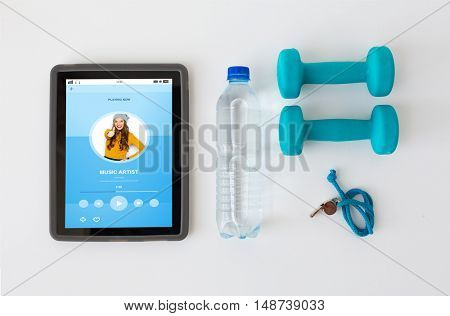 sport, healthy lifestyle, fitness and technology concept - tablet pc computer with dumbbells, whistle and water bottle over white background