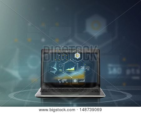 technology and statistics concept - laptop computer with virtual charts projection over dark gray background