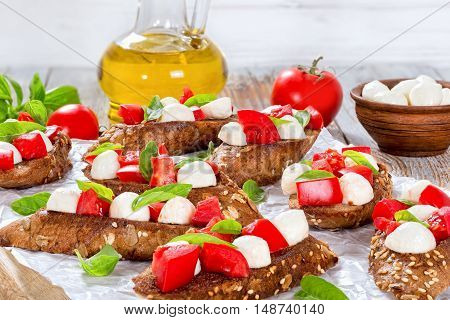bruschetta with tomatoes mozzarella and basil on fried in olive oil rye baguette with seeds on parchment paper. ingredients on peeling paint white planks italian recipe close-up top view