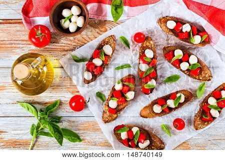 bruschetta with tomatoes mozzarella and basil on fried in olive oil rye baguette with seeds on parchment paper. ingredients on peeling paint white planks italian recipetop view