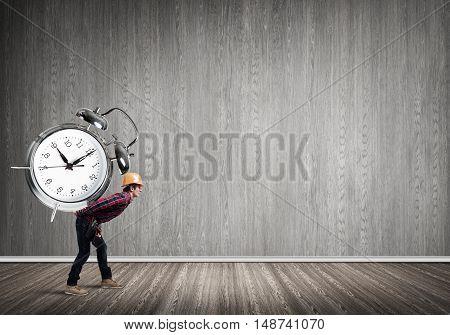 Builder man in helmet carrying alarm clock on back