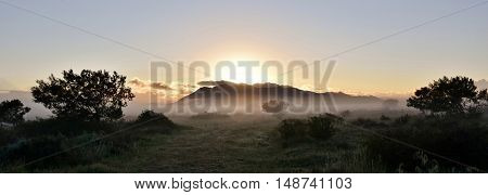 Landscape with fog and mountains on a cold winter morning