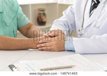 Hand of doctor reassuring him female patient. helping hand concept. medical concept.