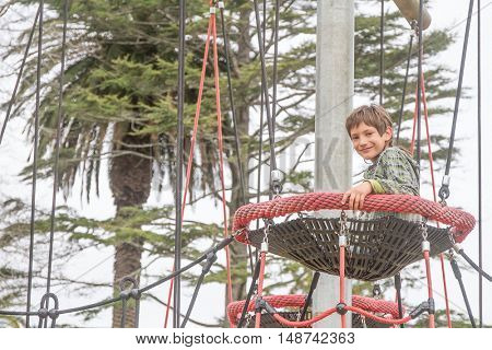 Challenging playground installation with nests and ropes for children to clamber. outdoor child boy portrait enjoying his time on the playground