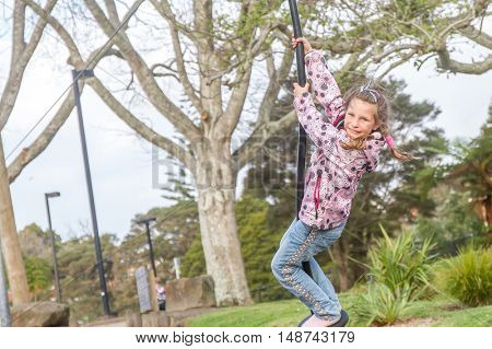 Happy Child blond girl rids on Flying Fox play equipment in a children's playground. Summertime