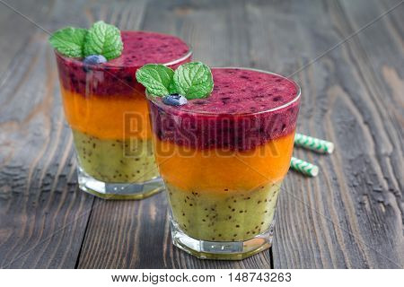 Triple smoothie in glass: kiwi-mint mandarin-apricot and strawberry-blueberry horizontal copy space