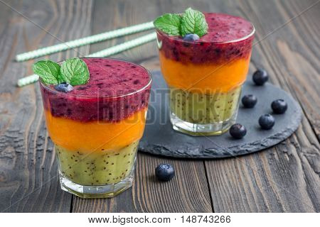 Triple smoothie in glass: kiwi-mint mandarin-apricot and strawberry-blueberry horizontal