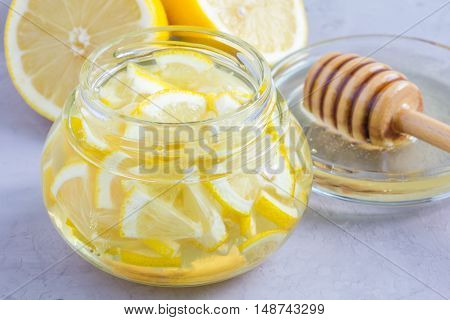 Lemon and honey mix for citrus tea in glass jar ingredients on background horizontal closeup