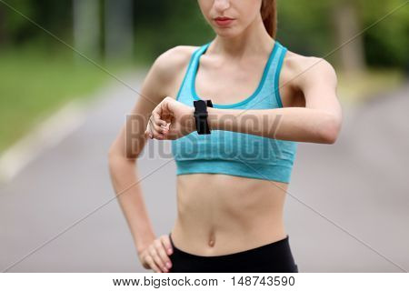 Young woman checking time after run in park