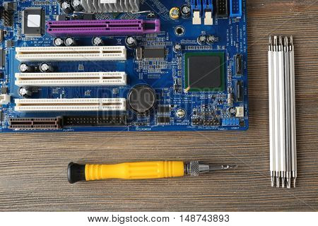 Motherboard, screwdriver and exchangeable bits on wooden background