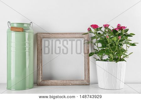 Vase with roses, watering can and photo frame on table