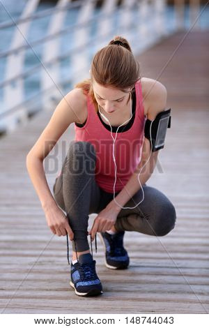 Young woman tying shoelaces on morning run