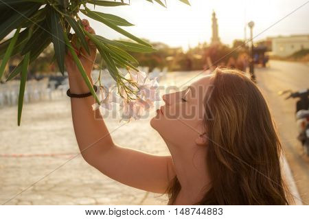 Young caucasian girl smelling pink flowers by street with eyes closed on sunset.