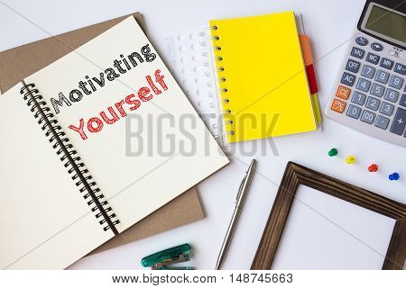 Text Motivating yourself on white paper book on table / business concept