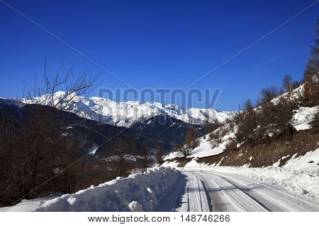 Ice-covered Road In Winter Snow Mountain At Sun Cold Morning