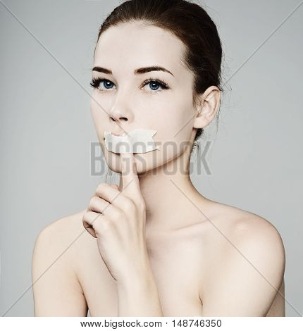 Beauty Woman Covers Her Mouth With A Finger. Face Portrait. Beautiful Spa Model Girl With Perfect Fr