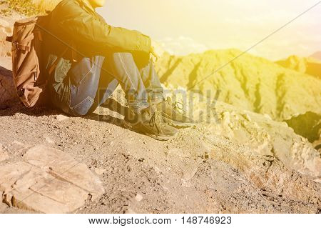Young traveler sitting on high hills and looking away at the village during sunset in Leh Ladakh India (Light Leak Orange tone)