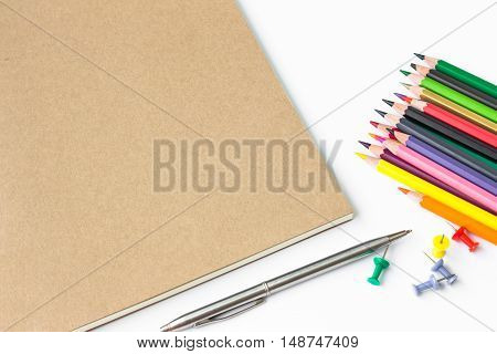 brown paper blank and paper note, color pencil, pen on white desk with copyspace / for your text or message, artwork / view from above, top view / business, office supplies concept