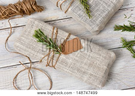 Fabric wrapped Christmas presents on a rustic wood table.