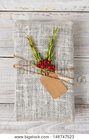 Fabric wrapped Christmas present on a rustic wood table.