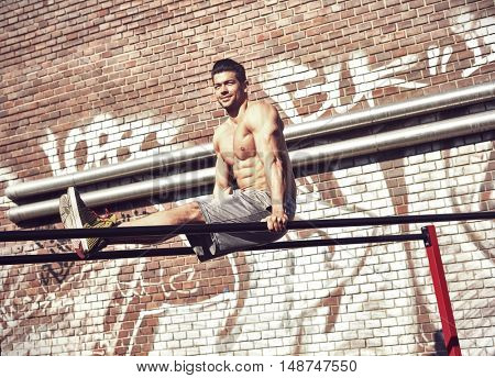 Street fitness workout young man doing exercise on parallel bars outdoors.