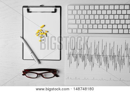Doctor's desk with keyboard, glasses, clipboard, drugs and cardiogram