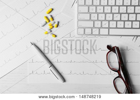 Doctor's desk with keyboard, glasses, pills and cardiogram