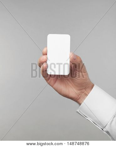 Man's hand holding white card on light background