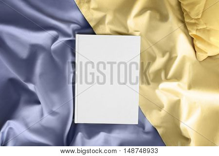 White closed book on crumpled sheet