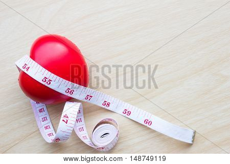 measuring tape around heart on wood table