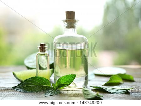 Bottles with mint oil, lime and fresh leaves on table