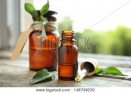 Bottles with mint oil and fresh leaves on blurred natural background