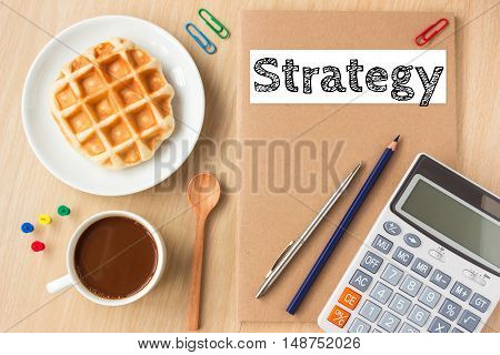 strategy text message on paper book and office supplies, pen, coffee on wood desk , copy space / business concept / view from above, top view
