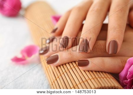 Female hands with brown manicure on wicker bamboo mat
