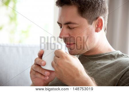 Handsome man sitting on couch with cup of coffee