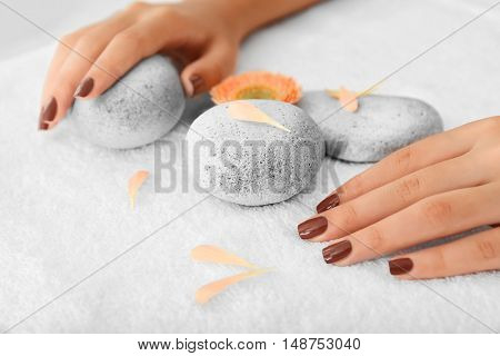 Female hands with brown manicure on spa stones, closeup