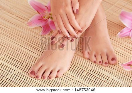 Female feet and hands with brown manicure on bamboo mat background