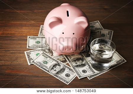 Pink piggy bank, glass of water and dollars on wooden background. Saving water concept