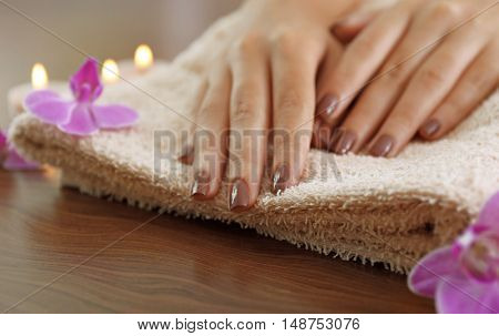 Female hands with brown manicure and orchid flowers on towel, closeup