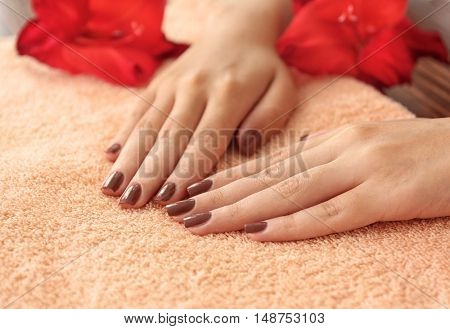 Female hands with brown manicure on towel, closeup