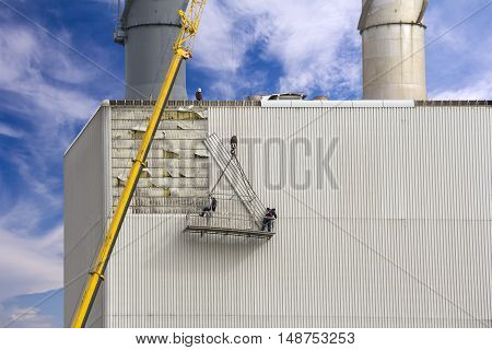 Workers hanging on the crane and repairing wall paneling on heating plant