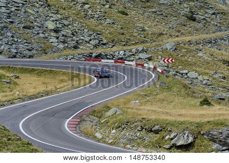 Driving on Transfagarasan mountain winding road, from Carpathian mountains in Romania in classic vintage sports.