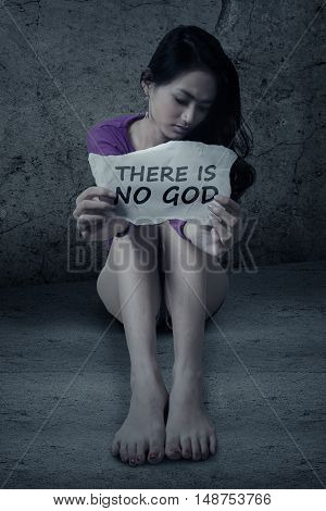 Image of atheist teenage girl sitting on the floor while holding a paper with text THERE IS NO GOD