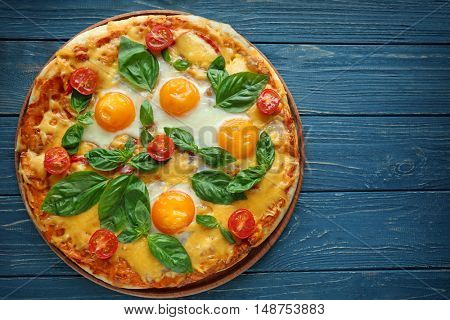 Margarita pizza with basil leaves and egg on wooden table, top view